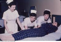 Student nurses seen taking a practical class in the demonstration room.