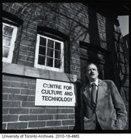 Marshall McLuhan in front of coach house