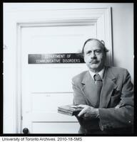 Marshall McLuhan in front of door to office