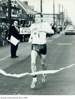 Bruce Kidd crossing the finish line at the 1963 Firestone War Vets Race.