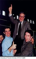 Bruce Kidd, Dean of the Faculty of Physical Education and Health, being lifted by two students.