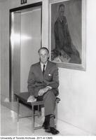 Dr. Kenneth G. McKenzie, seated in front of his 1953 portrait