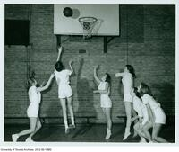 Jan (Thayer) Tennant (2nd from left) attempts a basket as part of a III PHE women's basketball team, 1957-1958