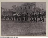 Early military drills on campus, shown here with partially built Hart House in the background