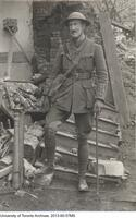 Prof . Roy Cockburn in front of destroyed house on the French Front.