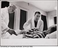 Dr. Frederick Kergin, at patient's bedside.