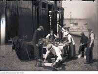 Scientists examining fish on dock