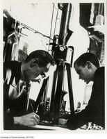 Albert Prebus (left) and James Hillier (right) working with the electron microscope in 1938.