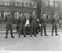 COTC cadets stand in front of a bren carrier with COTC Ball signage